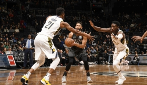 Allen Crabbe (center), Brooklyn Nets shooting guard, taking a shot surrounded by Pacers Thaddeus Young (left) and Victor Oladipo (right)