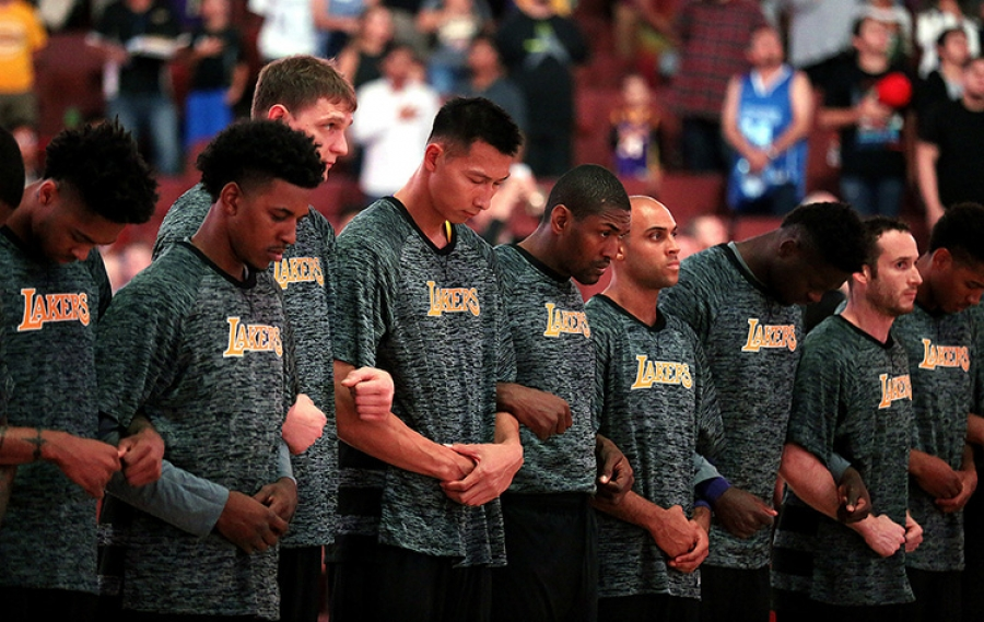 Los Angeles Lakers players standing arm-in-arm during the National Anthem at a preseason game
