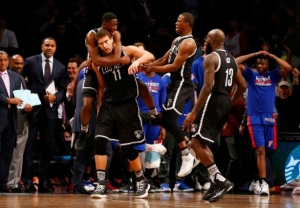 Brooklyn Nets center Brook Lopez is mobbed by teammates after he hits the buzzer-beating basket to lift the Nets to a 98-96 victory over the Detroit Pistons