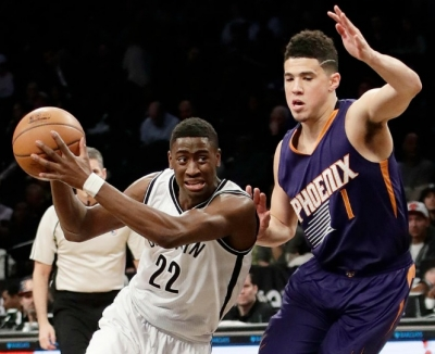 Caris LeVert of Brooklyn Nets being guarded by Phoenix Suns Devin Booker on March 23, 2017. Nets win 126-98