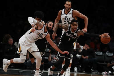 Brooklyn Nets guard D'Angelo Russell pushing the ball trying to get away from Utah Jazz defenders Ricky Rubio to the left and Rudy Gorbert on the right.