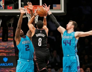 Brooklyn Nets guard Spencer Dinwiddie lifts between two Charlotte Hornets players, Marvin Williams (l) and Frank Kaminsky on the right, during an NBA basketball game at the Barclays Center in Brooklyn, NY on Friday, March 1, 2019, in New York.