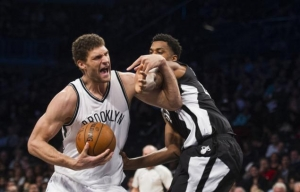 Brooklyn Nets center Brook Lopez defending off Miami Heat player