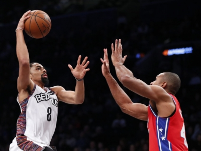 Spencer Dinwiddie, Brooklyn Nets guard going for a dunk with Philadelphia 76ers center Al Horford guarding basket at a game at the Barclays Center in Brooklyn, NY, on Sunday, December 15, 2019.