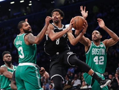 Spencer Dinwiddie (center) protecting the ball to pass around Marcus Morris (left) and Al Horford (right)