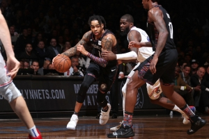 Brooklyn Nets guard D'Angelo Russell in traffic between two Philadelphia 76ers players and Nets Ed Davis (far right) looking on in Game 3 of the Eastern Conference NBA Playoffs on April 18, 2019, at the Barclays Center in Brooklyn, NY.