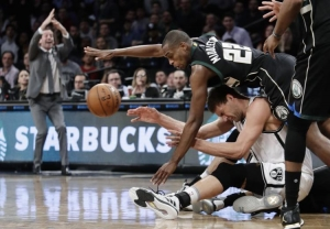 Brooklyn Nets center Brook Lopez on the floor and Milwaukee Bucks guard/forward Khris Middleton falling over Lopez struggling for the ball.