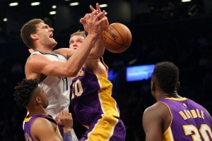 Brooklyn Nets center Brook Lopez fouled as he drives by Lakers center Timofey Mozgov at Barclays Center on December 14, 2016.