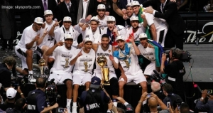 The San Antonio Spurs team with the winning 2014 NBA Championship trophy. The Spurs beat the Miami Heat 104-87