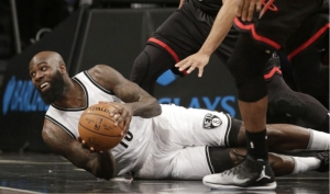 Brooklyn Nets' Quincy Acy, on the floor scrambling for the ball in a game against the Houston Rockets at the Barclays Center on Sunday, January 15, 2017.