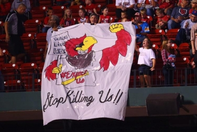 "Fan at a Cardinals-Brewers game displaying banner, ""Racism Lives Here"" and ""Stop Killing Us."""