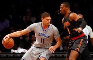 Brooklyn Nets center Brook Lopez trying to get past Atlanta Hawks center Dwight Howard