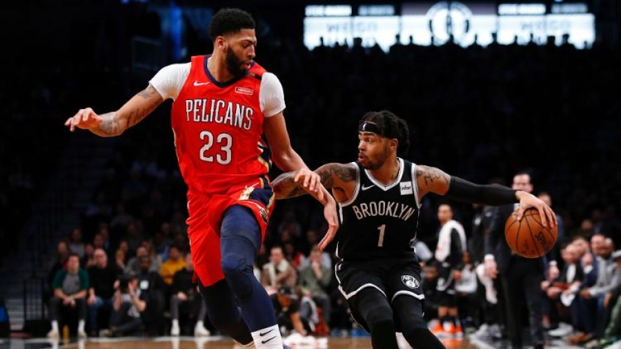 Brooklyn Nets guard D'Angelo Russell pushing past New Orleans Pelicans forward Anthony Davis (23) at a game at the Barclays Center on January 2, 2019.