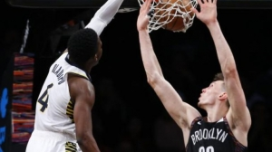 Brooklyn Nets rookie Rodions Kurucs attempting to block Indiana Pacers guard Victor Oladipo from scoring