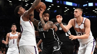 D'Angelo Russell, who led all scorers with 33 points in Nets loss to the Phoenix Suns, defending the ball against two Phoenix players