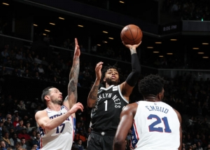 D'Angelo Russell, Brooklyn Nets point guard shooting ball over JJ Redick on left and Joel Embiid on right.
