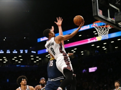 Brooklyn Nets guard, Spencer Dinwiddie, goes for a layup with Denver's Nikola Jokic defending at the Barclays Center on December 8, 2019. Brooklyn Nets defeat the Denver Nuggets 105-102.
