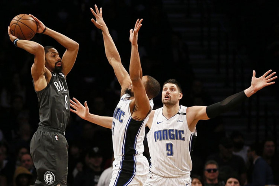 Brooklyn Nets guard, Spencer Dinwiddie, attempting to pass the basketball around Orlando Magic players Isaiah Briscoe (in center) and Nikola Vucevic (on the right)