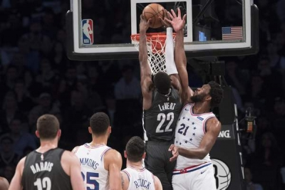 Caris LeVert, Brooklyn Nets guard, dunks ball despite the defensive efforts of Joel Embiid of the Philadelphia 76ers during Game 4 of the first round of the NBA Playoffs at Barclays Center on April 20, 2019.