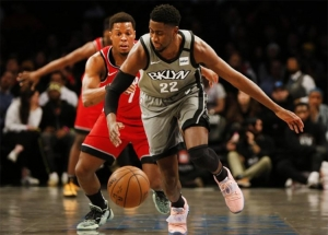 Brooklyn Nets guard, Caris LeVert, defends ball against Toronto Raptors guard, Kyle Lowry (in the background), at the Barclays Center in Brooklyn, NY on February 12, 2020.