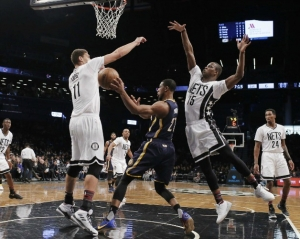 Brooklyn Nets center Brook Lopez (11) on left and Isaiah Whitehead (15) on right, surround Indiana Pacers forward Thaddeus Young (21).
