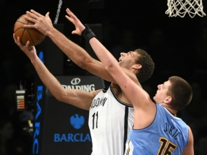 Brook Lopez leaps to the basket over Denver Nuggets forward Nikola Jokic (15) in the first half of an NBA basketball game at Barclays Center